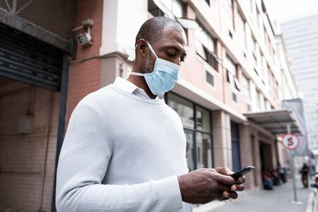African American man out and about in the city streets during the day, wearing a face mask against air pollution and covid19 coronavirus and using his smartphone.