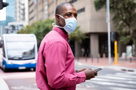 African American man out and about in the city streets during the day, wearing a face mask against air pollution and covid19 coronavirus, crossing the street and using his smartphone. Stock fotó
