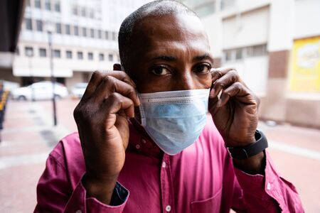 African American man out and about in the city streets during the day, putting on a face mask against air pollution and covid19 coronavirus and looking straight into a camera.