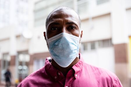 Portrait of African American man out and about in the city streets during the day, wearing a face mask against air pollution and covid19 coronavirus, looking straight into a camera.