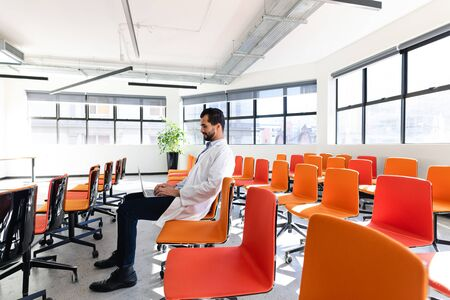 Side of a Caucasian male medical professional wearing lab coat, sitting in an empty modern conference room, talking and using laptop.