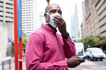 African American man out and about in the city streets during the day, wearing a face masks against air pollution and covid19 coronavirus, covering his face and using his smartphone. Stock fotó