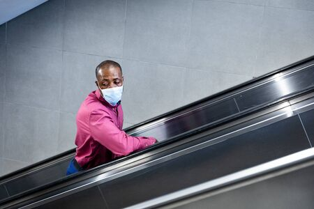 African American man wearing a face masks against air pollution and covid19 coronavirus, standing on escalator and leaning on a handrail. Stock fotó
