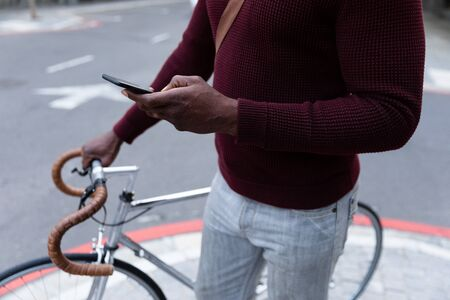 Mid section of African American man out and about in the city streets during the day, wheeling his bicycle and using a smartphone.
