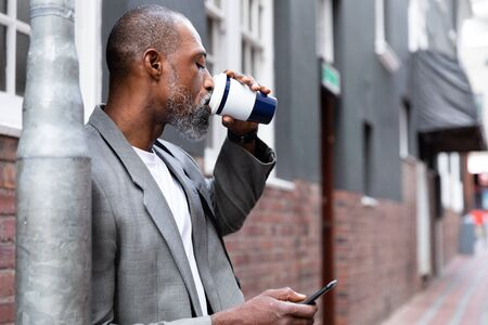 African American man out and about in the city streets during the day, standing on the street, drinking a takeaway coffee and using his smartphone. Stock fotó
