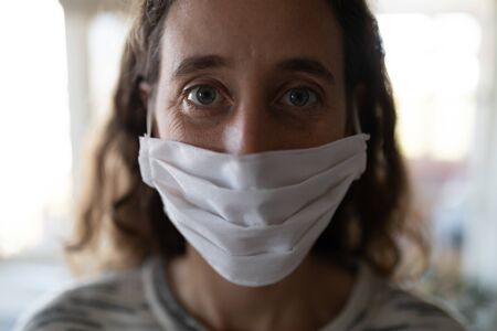 Portrait of Caucasian woman spending time at home self isolating and social distancing in quarantine lockdown during coronavirus covid 19 epidemic, wearing a face mask and looking at camera