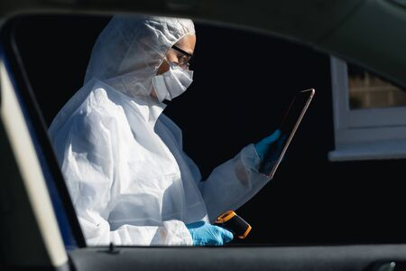 Caucasian woman wearing lab overalls and a face mask face standing outside by a car, using tablet and holding thermometer
