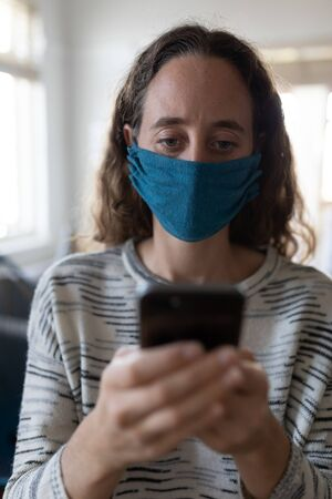 Caucasian woman spending time at home self isolating and social distancing in quarantine lockdown during coronavirus covid 19 epidemic, wearing a face mask and using smartphone