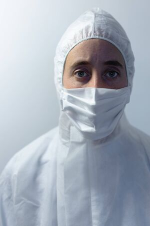 Portrait of a Caucasian woman wearing lab overalls and a face mask standing in an empty white room, looking at camera