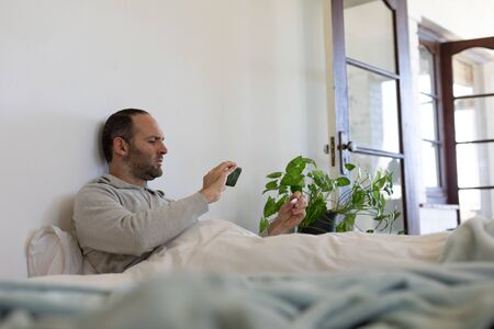Sick Caucasian man spending time at home self isolating and social distancing in quarantine lockdown during coronavirus covid 19 epidemic, in bed holding a thermometer and using his smartphone Stock Photo