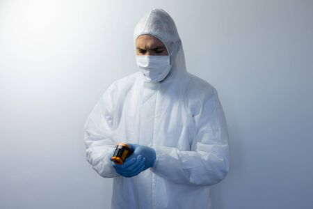 Caucasian man wearing lab overalls and a face mask standing in an empty white room, wearing gloves and checking thermometer Stock Photo