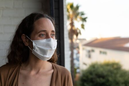 Caucasian woman spending time at home self isolating and social distancing in quarantine lockdown during coronavirus covid 19 epidemic, wearing a face mask and standing on her balcony Stock Photo