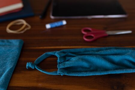 Close up of a diy mask, a blue material, a thread and scissors lying on a wooden table, used for making face masks against covid 19