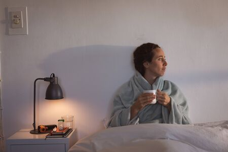 Sick Caucasian woman spending time at home self isolating and social distancing in quarantine lockdown during coronavirus covid 19 epidemic, holding a mug