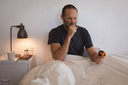 Sick Caucasian man spending time at home self isolating and social distancing in quarantine lockdown during coronavirus covid 19 epidemic, sitting up in bed checking his temperature and coughing Stock Photo