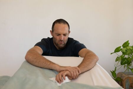 Sick Caucasian man spending time at home self isolating and social distancing in quarantine lockdown during coronavirus covid 19 epidemic, sitting up in bed with eyes closed