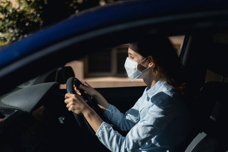 Caucasian woman sitting in a car and driving, wearing a face mask against covid 19 and a blue shirt on a sunny day