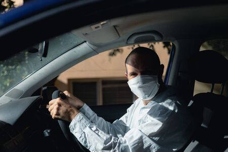 Caucasian man sitting in a car and driving, wearing a face mask against covid 19 and a white shirt on a sunny day, looking at camera Stock Photo