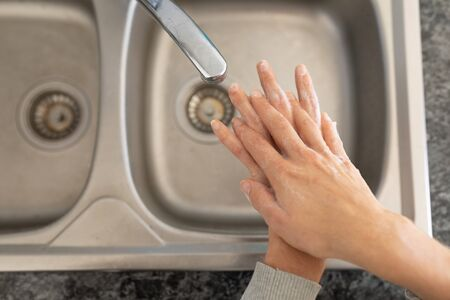 Hands of a Caucasian woman spending time at home self isolating and social distancing in quarantine lockdown during coronavirus covid 19 epidemic, washing her hands in her kitchen
