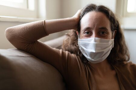 Portrait of Caucasian woman spending time at home self isolating and social distancing in quarantine lockdown during coronavirus covid 19 epidemic, sitting on a sofa, wearing a face mask and looking at camera