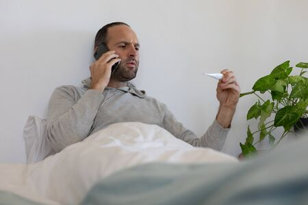 Sick Caucasian man at home self isolating and social distancing in quarantine lockdown during coronavirus covid 19 epidemic, sitting up in bed talking on smartphone and holding a thermometer