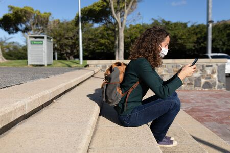 Caucasian woman out and about in the city streets during the day, wearing a face mask against covid19 coronavirus sitting and using her smartphone in park Stock Photo