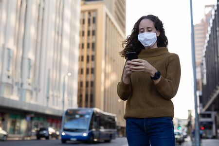 Caucasian woman out and about in the city streets during the day, wearing a face mask against covid19 coronavirus standing and using her smartphone Stock Photo