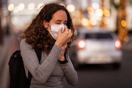Caucasian woman out and about in the city streets during the day, wearing a face mask against air covid19 coronavirus standing beside a road