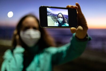 Caucasian woman out and about in the city streets in the evening, wearing a face mask against covid19 coronavirus, taking selfie with her smartphone, focus on the foreground