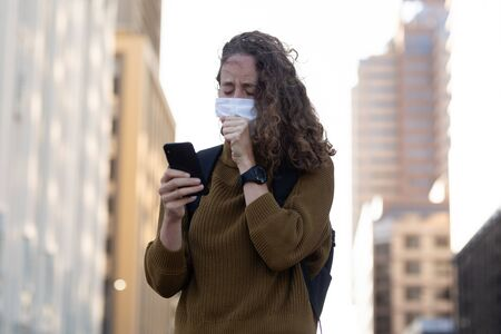 Caucasian woman out and about in the city streets during the day, wearing a face mask against covid19 coronavirus covering her face while coughing and using smartphone