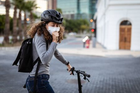 Caucasian woman out and about in the city streets during the day, wearing a cycling helmet and a face mask against covid19 coronavirus, standing with her bicycle and covering her face while coughing