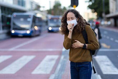 Caucasian woman out and about in the city streets during the day, wearing a face mask against covid19 coronavirus covering her face while coughing