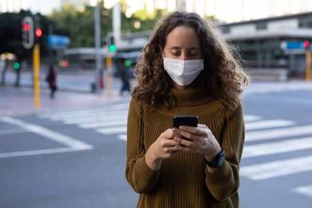 Caucasian woman out and about in the city streets during the day, wearing a face mask against covid19 coronavirus standing and using her smartphone 免版税图像