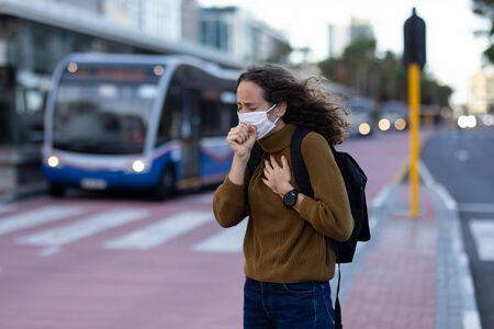 Femme caucasienne dans les rues de la ville pendant la journée, portant un masque facial contre le coronavirus covid19 couvrant son visage en toussant Banque d'images