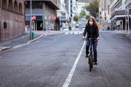 Caucasian woman out and about in the city streets during the day, wearing a face mask against air pollution and covid19 coronavirus, cycling Stock Photo
