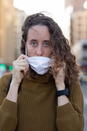 Portrait close up of Caucasian woman out and about in the city streets during the day, putting on a face mask against covid19 coronavirus, looking straight to camera