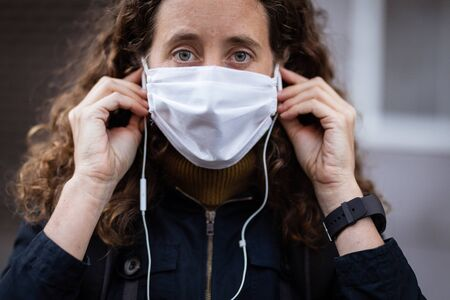 Portrait of Caucasian woman out and about in the city streets during the day, wearing a face mask against covid19 coronavirus, putting on her earphones