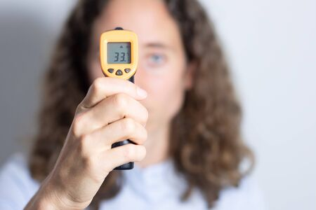 Portrait of a Caucasian woman with long curly hair, examining her temperature, holding a non contact gun thermometer, social distancing and self isolating during coronavirus outbreak.