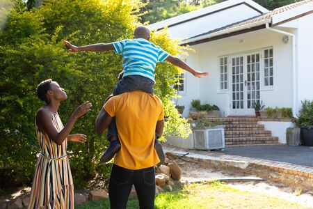 African American woman spending time with her partner who is giving their son a piggyback in the garden. Social distancing and self isolation in quarantine lockdown.