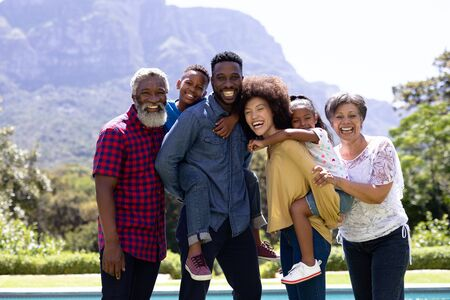 Multi-generation mixed race family enjoying their time at a garden with a pool, standing by the pool, embracing, looking at the camera and smiling, parents are holding their children piggy back