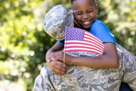 African American man wearing a military uniform, returning home, holding his son up, embracing, looking at the camera and smiling, a boy is holding a mini flag, on a sunny day