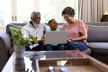 Mixed race boy and his grandparents enjoying their time at home together, sitting on a couch, using a laptop, looking at each other and smiling