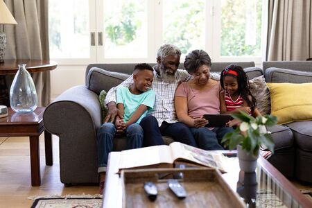 Senior mixed race couple with their grandchildren, enjoying their time at home together, sitting on a couch, embracing, using a digital tablet
