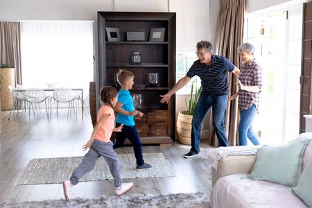 Caucasian girl and boy running through the sitting room, welcoming their grandparents entering their house. Standard-Bild