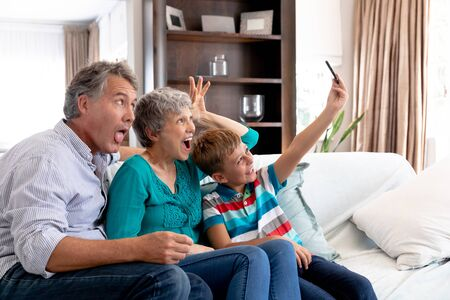Senior Caucasian couple and their grandson spending time at home, sitting on a couch in the sitting room and taking a selfie with a smartphone.