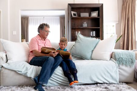 Senior Caucasian man spending time at home with his grandson, sitting on a couch and watching a family album.