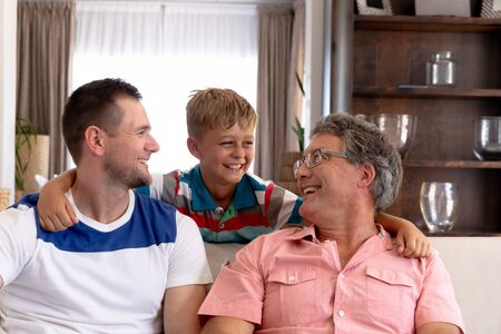 Senior Caucasian man spending time with his son and his grandson at home in the sitting room, smiling and embracing. Standard-Bild