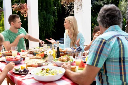 Caucasian three generation family having a lunch in the garden on a sunny day, sitting by a table and interacting. Foto de archivo