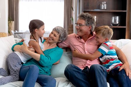 Caucasian girl and boy spending time together with their grandparents, sitting on a couch in the sitting room, embracing and smiling. Standard-Bild