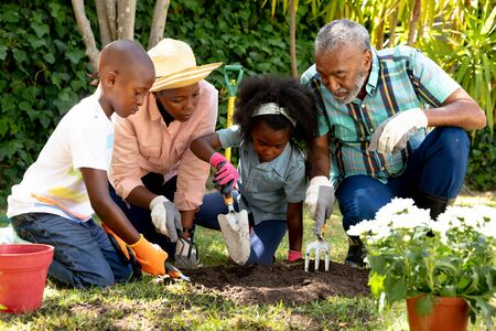 Senior African American couple spending time with their granddaughter and grandson in the garden on a sunny day, planting flowers.